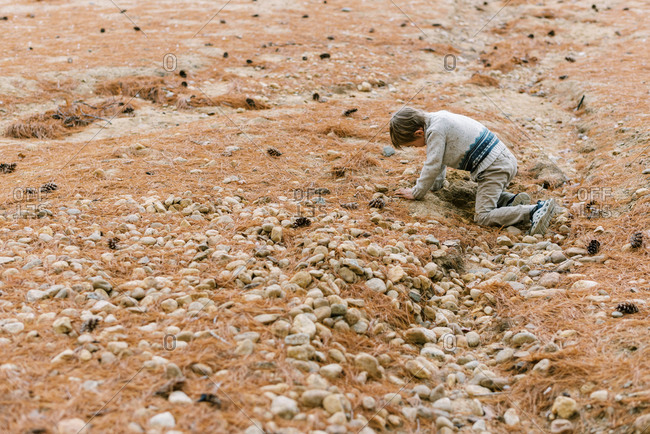 A little boy digging in the sand for more rocks