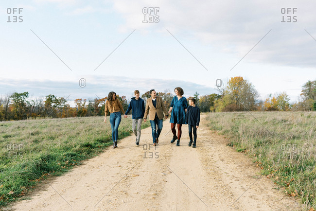 A happy family of five holding hands together on a path