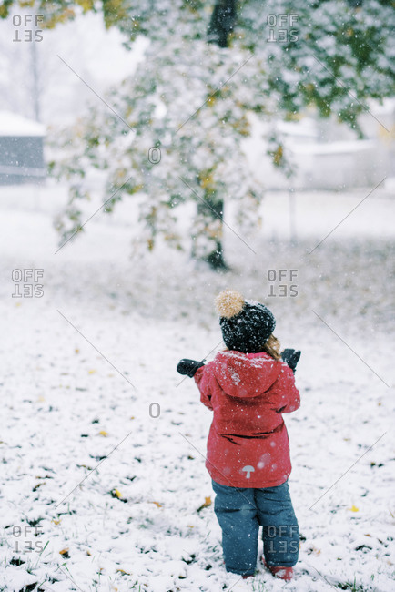 Little girl experiencing a snowfall in October in new England