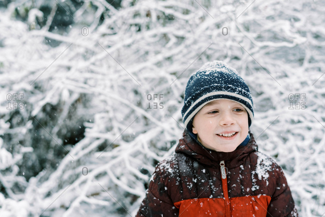 Little boy experiencing a snowfall in October in new England