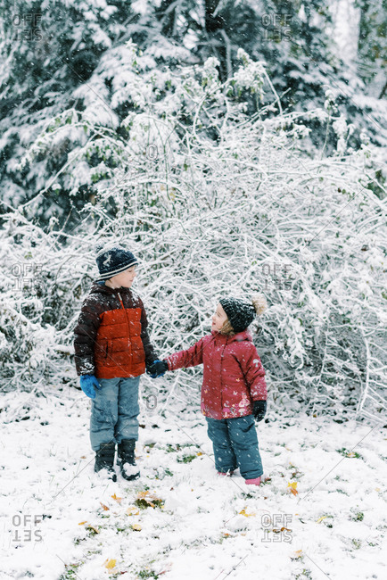 Little kids experiencing a snowfall in October in new England