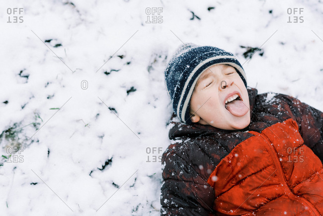 Little boy lying in the snow trying to catch snowflakes
