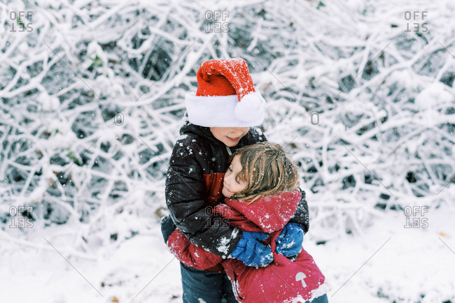 Little kids playing during a snowfall outside wearing a santa hat