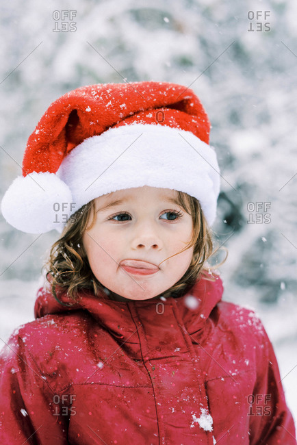 Little girl wearing a santa hat during a snowfall outside in winter