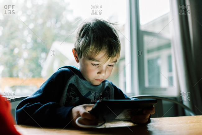 Little boy playing video games on his tablet