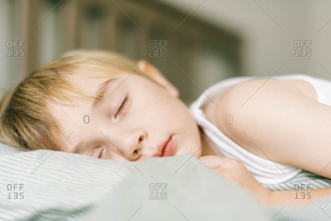 Little blonde boy sleeping in his bed