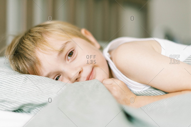 Happy little boy getting ready for a nap in bed