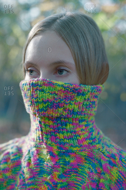 Woman hiding her face in a sweater while standing in the autumn forest