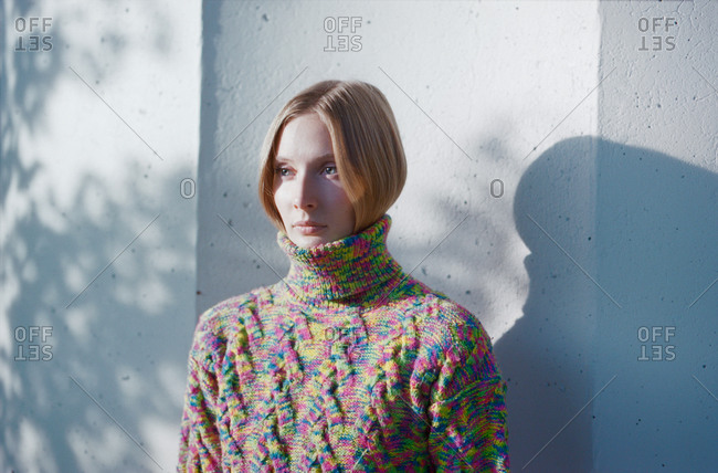 Blond woman in a sweater standing near a concrete wall in the forest.