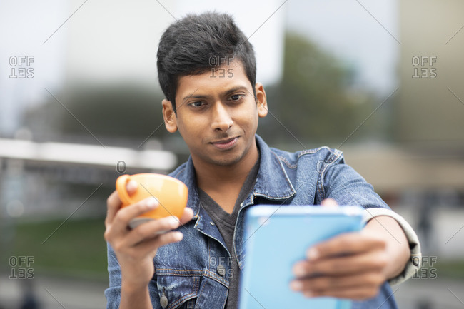 Young man sitting outside in the city with tablet and cup