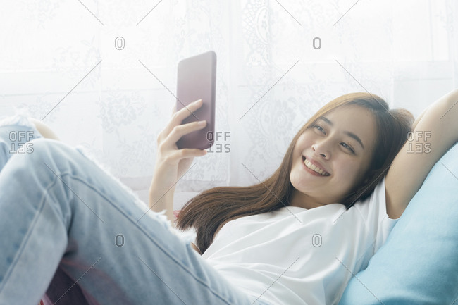 Attractive smiling Asian woman using smart phone on the relaxing