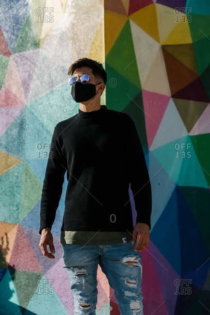 Boy with sunglasses and mask posing in front of a painted wall