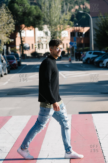 Boy with sunglasses crossing a zebra crossing