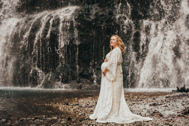 Pregnant woman standing in front of waterfall in winter touching belly