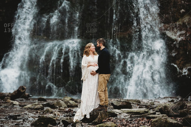 Expecting couple outside in winter by a waterfall standing on rocks