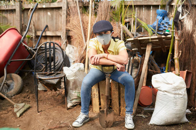 Young woman using mask face taking a break after gardening