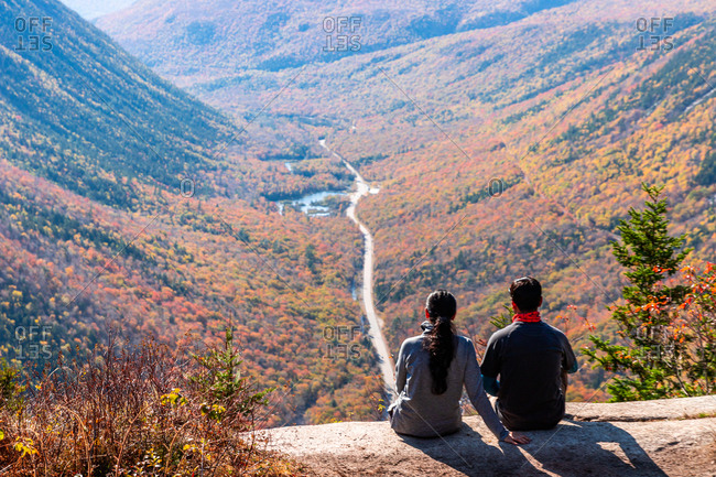 Hiking couple sitting on mountain ledge looking out over valley in nh.