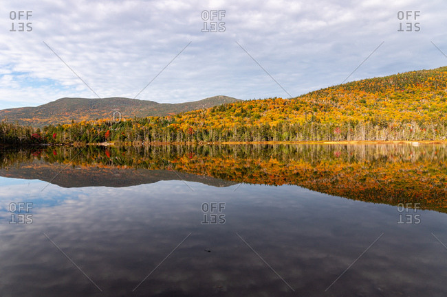 Colorful trees in the white mountains reflecting in calm lake water.