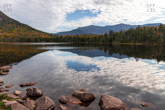 Mountains and trees reflecting in calm lake water during peak foliage.