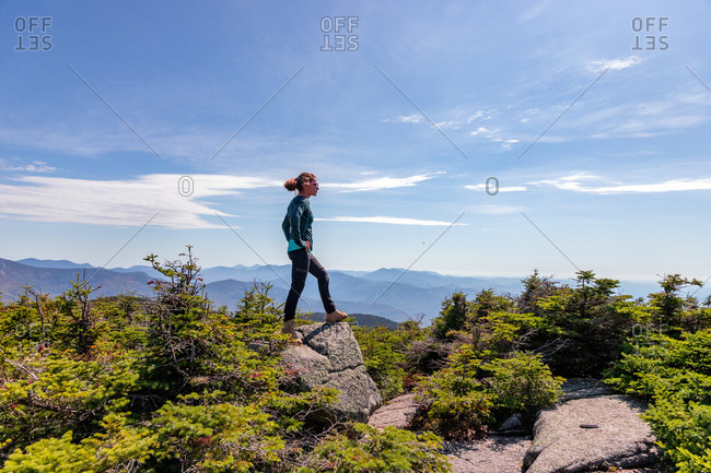 Young woman standing at top of mountain staring out at peaks beyond.