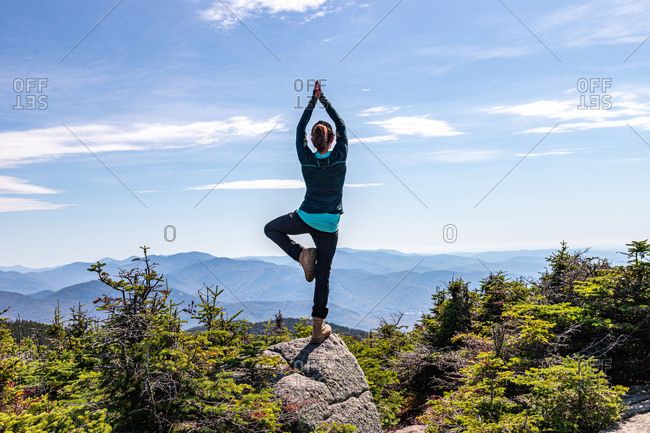 Young woman practicing yoga balancing on one leg at top of mountain.