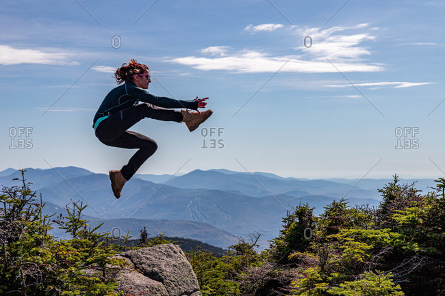 Young woman jumping off boulder in the white mountains.
