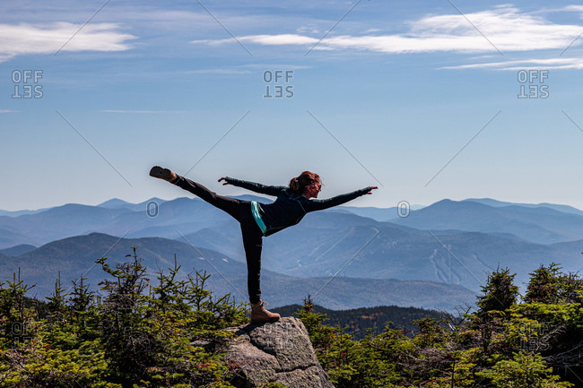 Young athletic woman balancing on one leg at top of mountain peak.