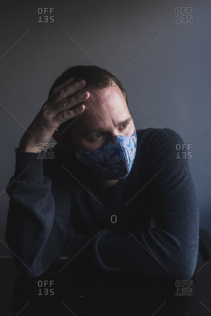 Portrait of white man worried about pandemic and using mouth cover