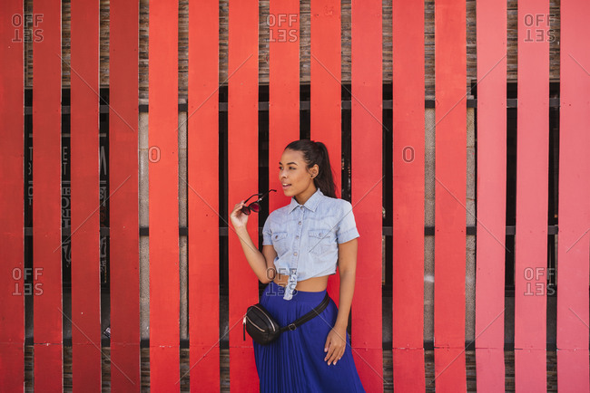Portrait of cute Hispanic woman with red background