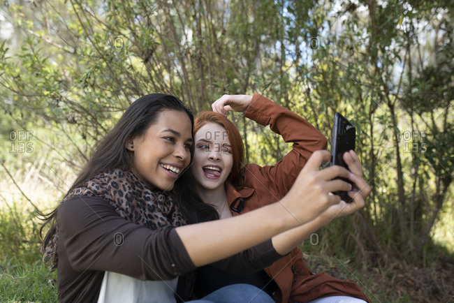Two multiracial women making a selfie in the park