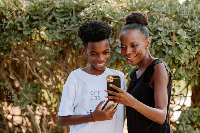 Smiling black mom and preteen son looking at cellphones together