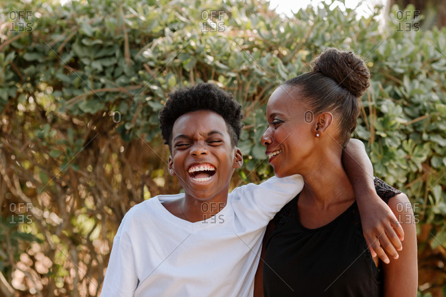 Laughing African American boy in white t-shirt hugging smiling mother