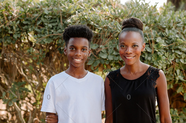 Beautiful African American mom  outdoors with smiling preteen son