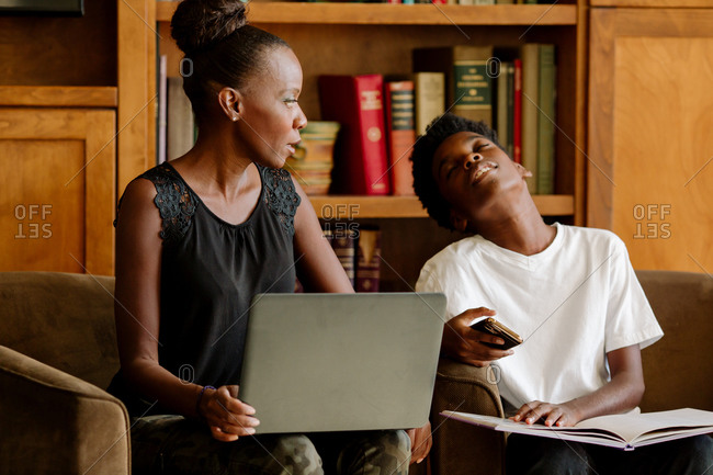 Black mom with computer homeschooling tired preteen son holding Phone