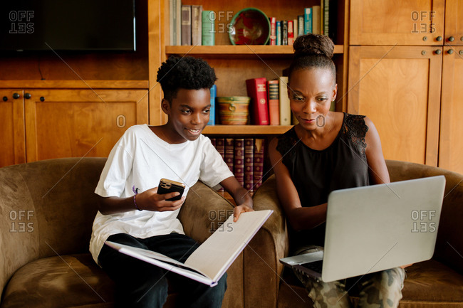 African American mom with laptop helps son during distance learning