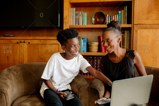 Black mom and preteen son smiling together during distance learning