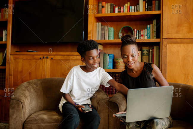 Happy African American boy & mom with laptop during distance learning