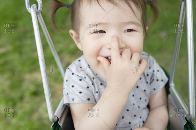 Adorable Baby Girl Smiles with Hand Over Mouth While Swinging Outdoors