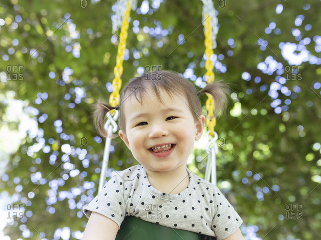 Happy Smiling Toddler Girl with Pigtails Swings Outdoors Under A Tree