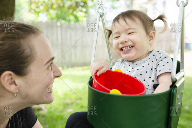 Toddler Age Girl with Pigtails Laughs While Sitting in Swing Near Mom