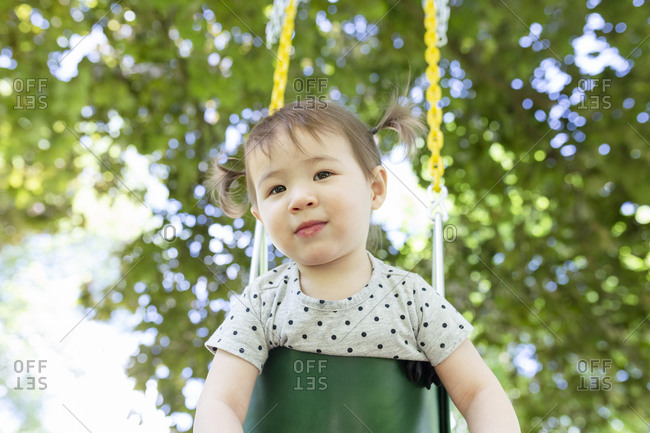 Adorable Toddler Girl with Ponytails Looks While Sitting in Swing