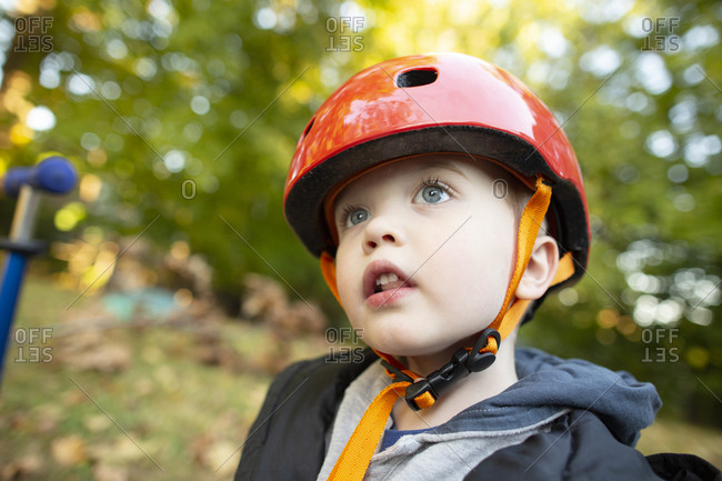 Preschool Age Boy Wearing Red Helmet Looks Up While Outside Playing