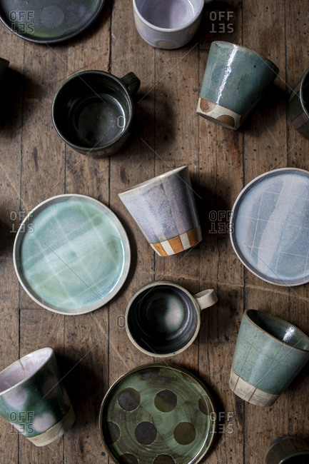 Selection of ceramic mugs, cups, and plates on wood surface