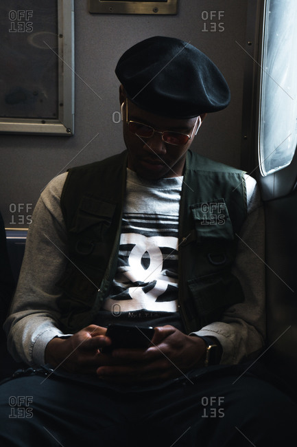 New York, NY, United States - May 23, 2019: Young black man sitting in the metro