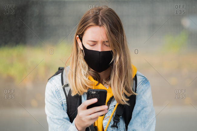 Woman in mask with a cell phone.