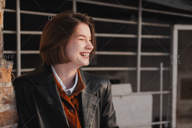 Happy smiling woman in leather jacket, direct sunlight and nature
