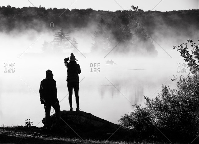 Man and woman view fog shrouded Vermont lake as fishermen paddle out
