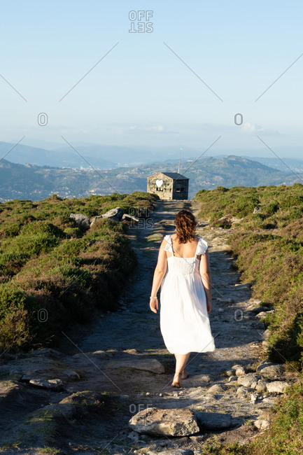 Rear view of a woman in white dress walking on a path in the mountain