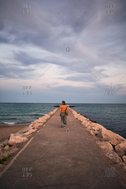 Middle-aged woman walks on a catwalk on the coast