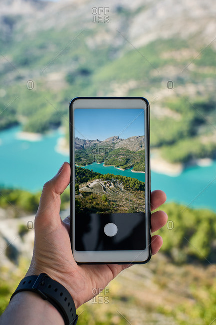 Close-up of a cell phone with a photo of a lake